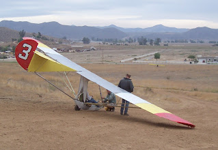 Photo: Flight instruction is underway in Goat3 at a training hill, November 2006. The Goat nose is down on the ground, as it is at the beginning and end of most flights. This rolling launch will allow a brief floating flight before a landing in the grassy field. Notice the yellow hang glider which has just landed out in front.