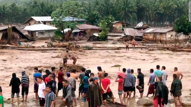 Villagers cross raging floodwaters 22 December 2017 in Lanao del Norte province in the southern Philippines in this photo made from video by Aclimah Disumala. Photo: Aclimah Disumala / AP
