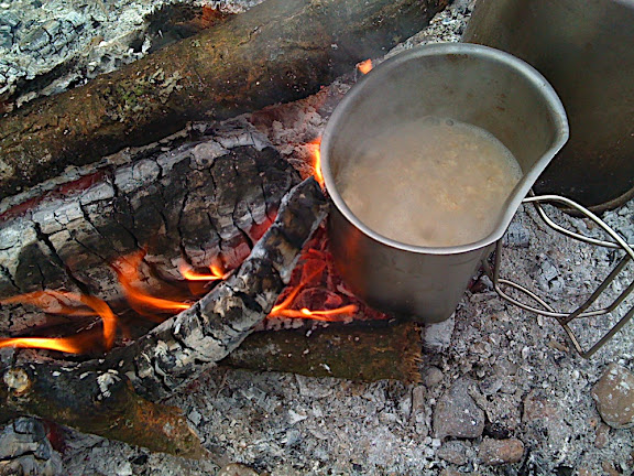 Porridge cooking on the fire in a steel 'crusader' mug.