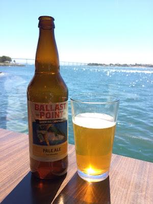 Et glass og en flaske med øl med sjøen i bakgrunnen.