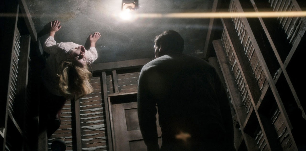 Lulu Wilson as Doris and Henry Thomas as Father Tom in OUIJA: ORIGIN OF EVIL. (Photo courtesy of Universal Pictures).