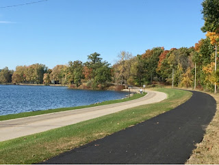 Blue lake in Hilldale Michigan with road and paved walking path amidst forest of tree in full fall colors