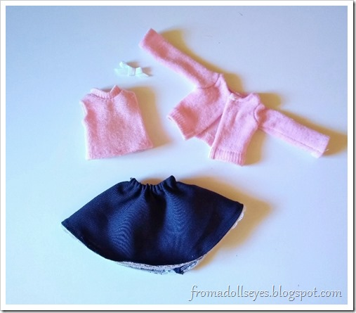 The completed ball jointed doll outfit of sleeveless pink top, matching pink sweater, navy blue skirt and ribbon pin.