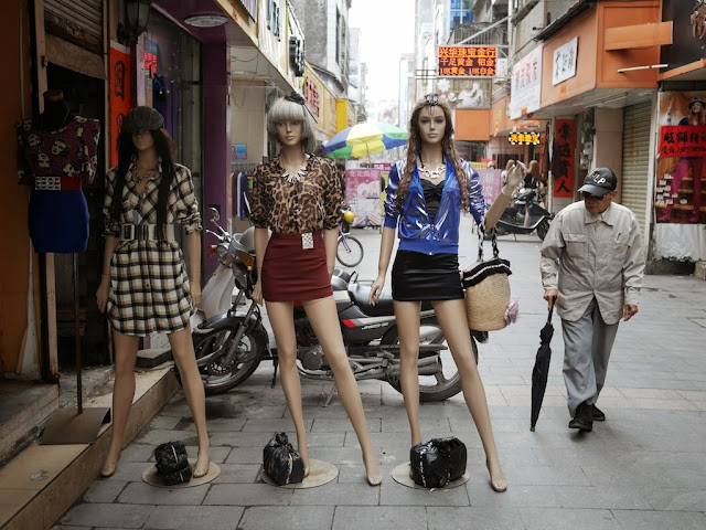 older man with umbrella walking past mannequins in Yangjiang, China
