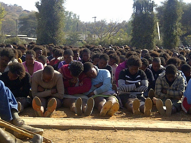 Bojale initiates seated in their subservient posture, exhausted