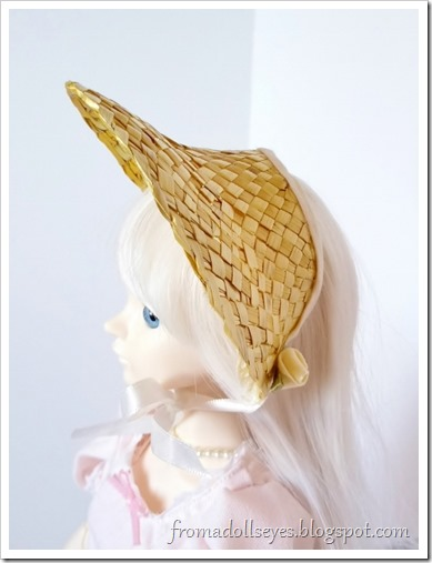 One of the bonnets worn by a bjd (Hikaru).  There is white ribbon on the bonnet that ties in a bow under her chin and matching white roses on the bonnet.