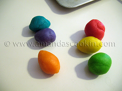 A close up photo of red, yellow, orange, green, purple and blue cookie dough balls.