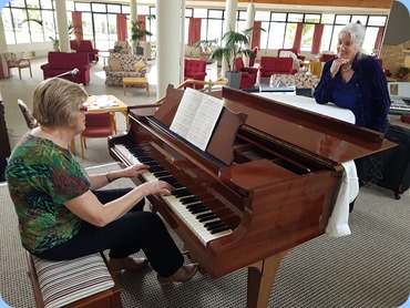 The Club's Events Manager, Kay Boyes, playing the Steinway grand piano whilst Club Secretary, Delyse Whorwood listens-on enjoying Richard Clayderman's Ballade Pour Adeline.