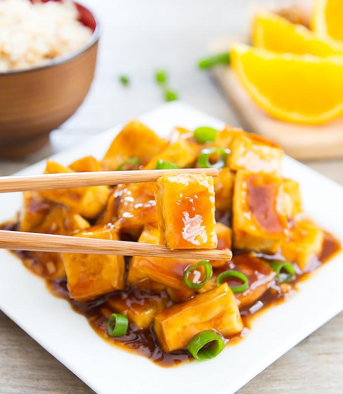 a pair of chopsticks holding a piece of crispy baked orange tofu