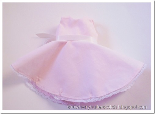 A pink vintage style dress for a doll.