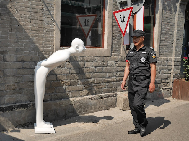security guard walking by a 让 (yield) sign and a sculpture of a smiling forward-leaning bald human (either by Gao Xiaowu or an imitation)