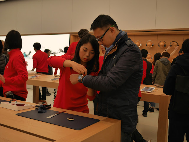 Apple employee helping a man put on an Apple Watch