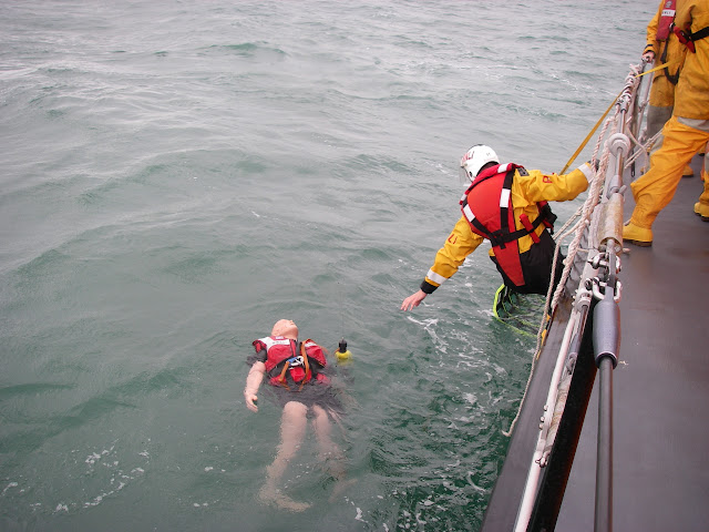 17 July 2011 – Crew Member Scott Rowland getting ready on the scramble net to retrieve our casualty dummy and tracking device from the water off Poole's all-weather lifeboat. Fortunately our lookout skills located the casualty and we didn't lose her! Photo: RNLI Poole/Anne Millman
