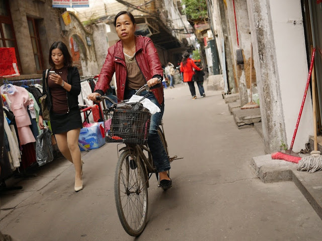 Woman on bicycle passing a woman looking at her mobile phone at Wuya Lane in Shaoguan, Guangdong