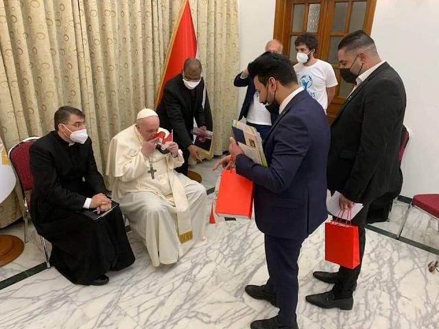 البابا فرنسيس يُقبل العلم العراقي عقب زيارته الى مدينة اور التاريخية.