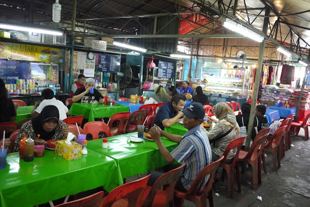people eating at tables at Bazaar Baru Chow Kit in Kuala Lumpur, Malaysia
