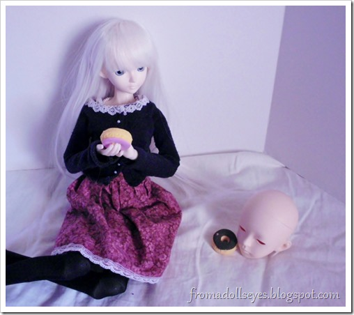 A ball jointed doll eating a donut with a head.
