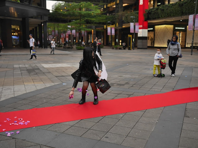 woman spreads petals on a red carpet