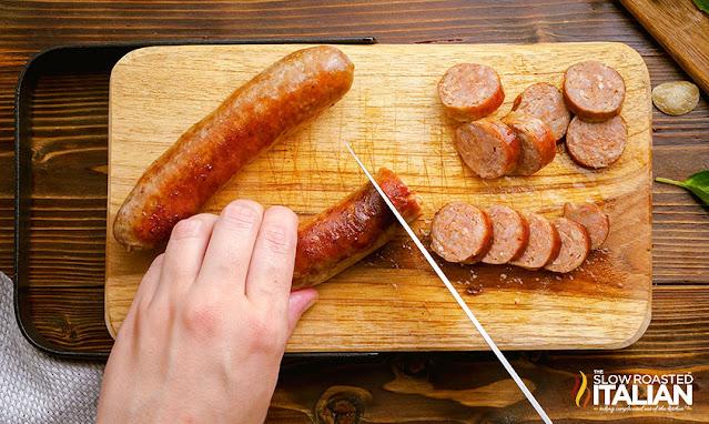 slicing sausage on a cutting board