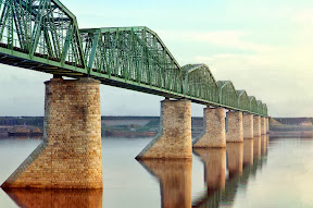 Металлический мост со сквозной фермой на каменных опорах – часть Транс-Сибирской железной дороги – пересекает реку Кама, недалеко от Перми