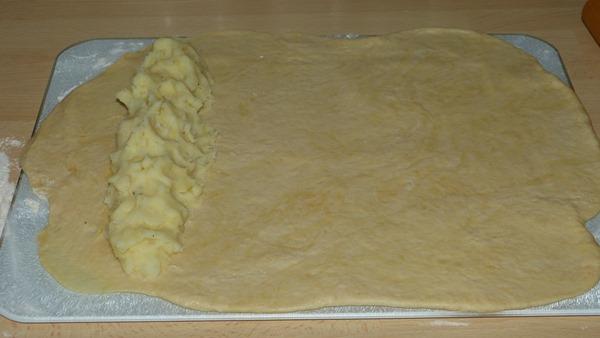 Раскатанное дрожжевое тесто с выложенной начинкой