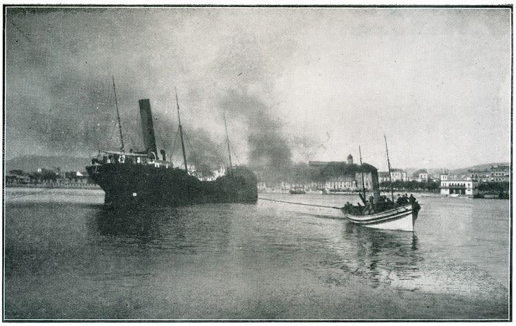 El TIFLIS incendiado en Alicante y remolcado hacia el exterior del puerto por un pesquero. Foto de la revista La Actualidad de fecha desconocida.jpg