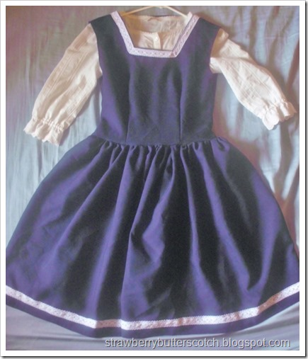 A cute school-like jumper style dress made with navey blue poly poplin and trimmed with crocheted lace.