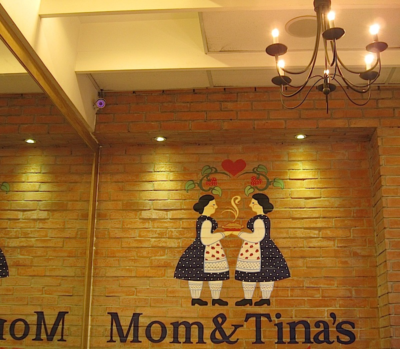 colour logo of Mom & Tina's Bakery & Café painted on a brick wall