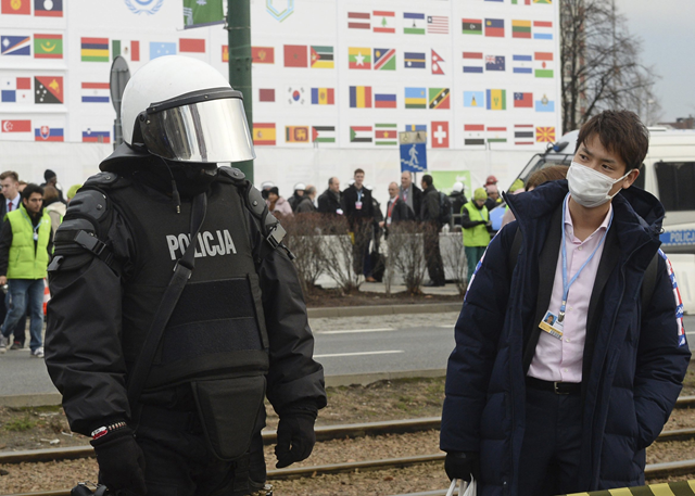 A climate conference participant looks at a police officer during the March for Climate, a protest against global warming in Katowice, Poland, Saturday, 8 December 2018, as the COP24 UN Climate Change Conference takes place in the city. Photo: Alik Keplicz / AP Photo