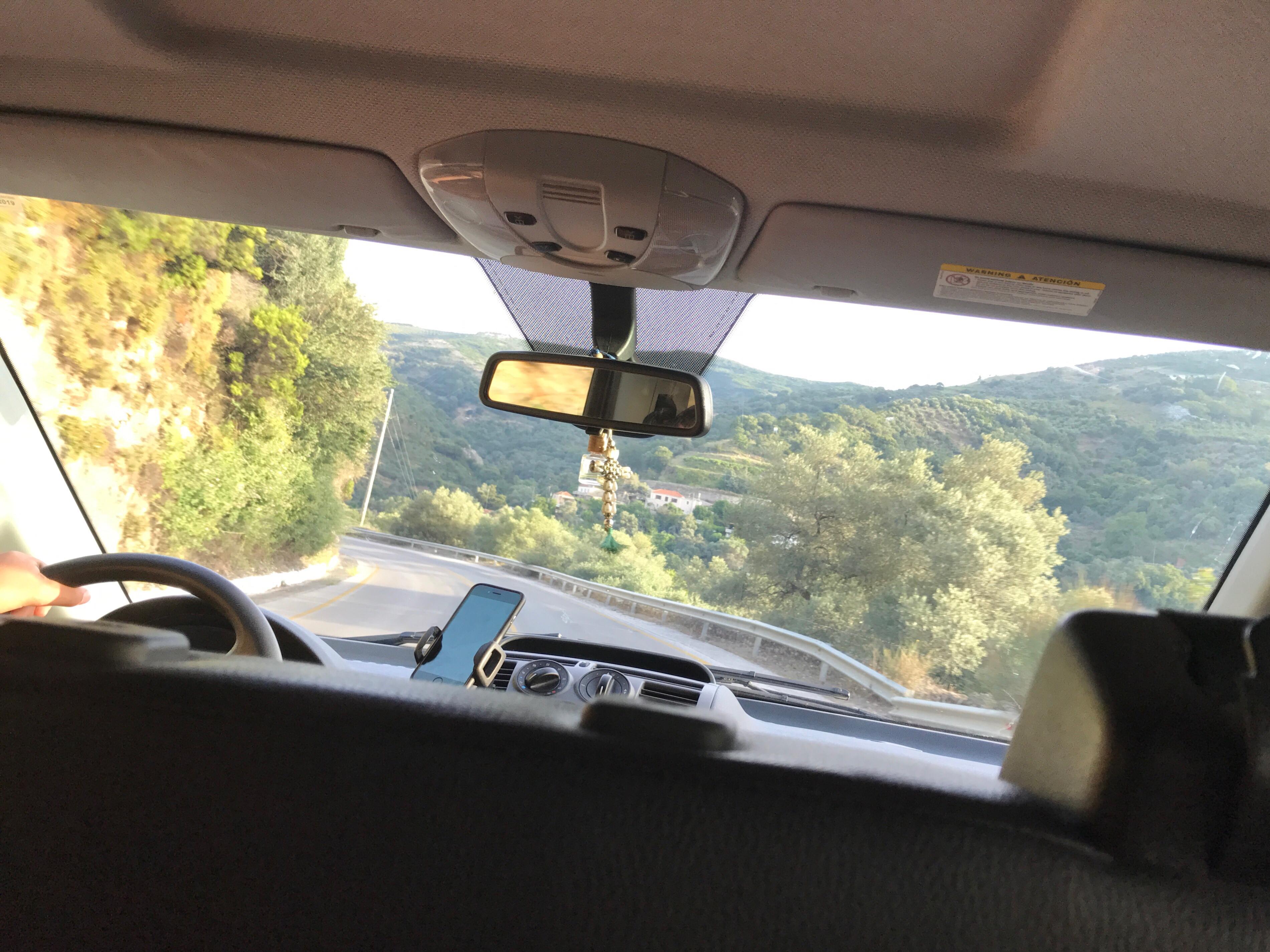 Bilde tatt gjennom frontruta på en bil. Skogkledt fjellandskap utenfor.