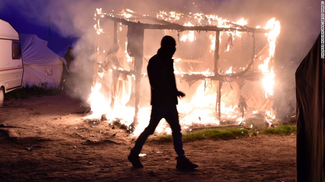 A migrant walks past a shack set ablaze in the Calais refugee camp known as 'the Jungle', on Tuesday night, 26 October 2016. Photo: Philippe Huguen / AFP / Gerry Images