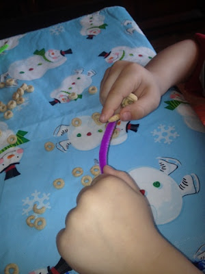 thread O -shaped cereal on pipe cleaners