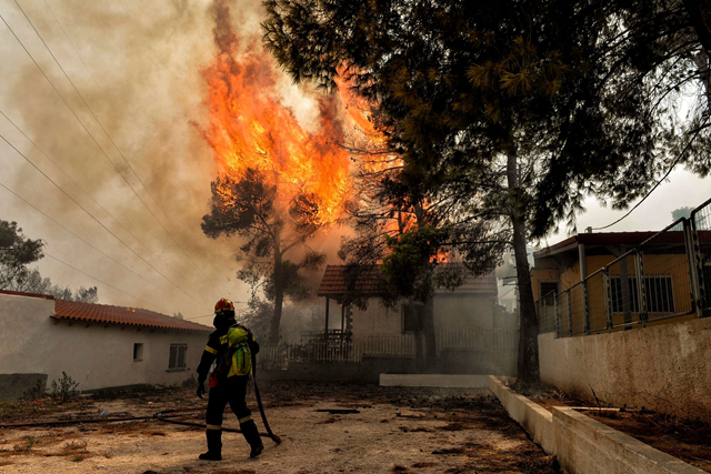 A firefighter working on Monday, 23 July 2018, to quell flames in Kineta, a coastal city west of Athens. Photo: Valerie Gache / Agence France-Presse / Getty Images