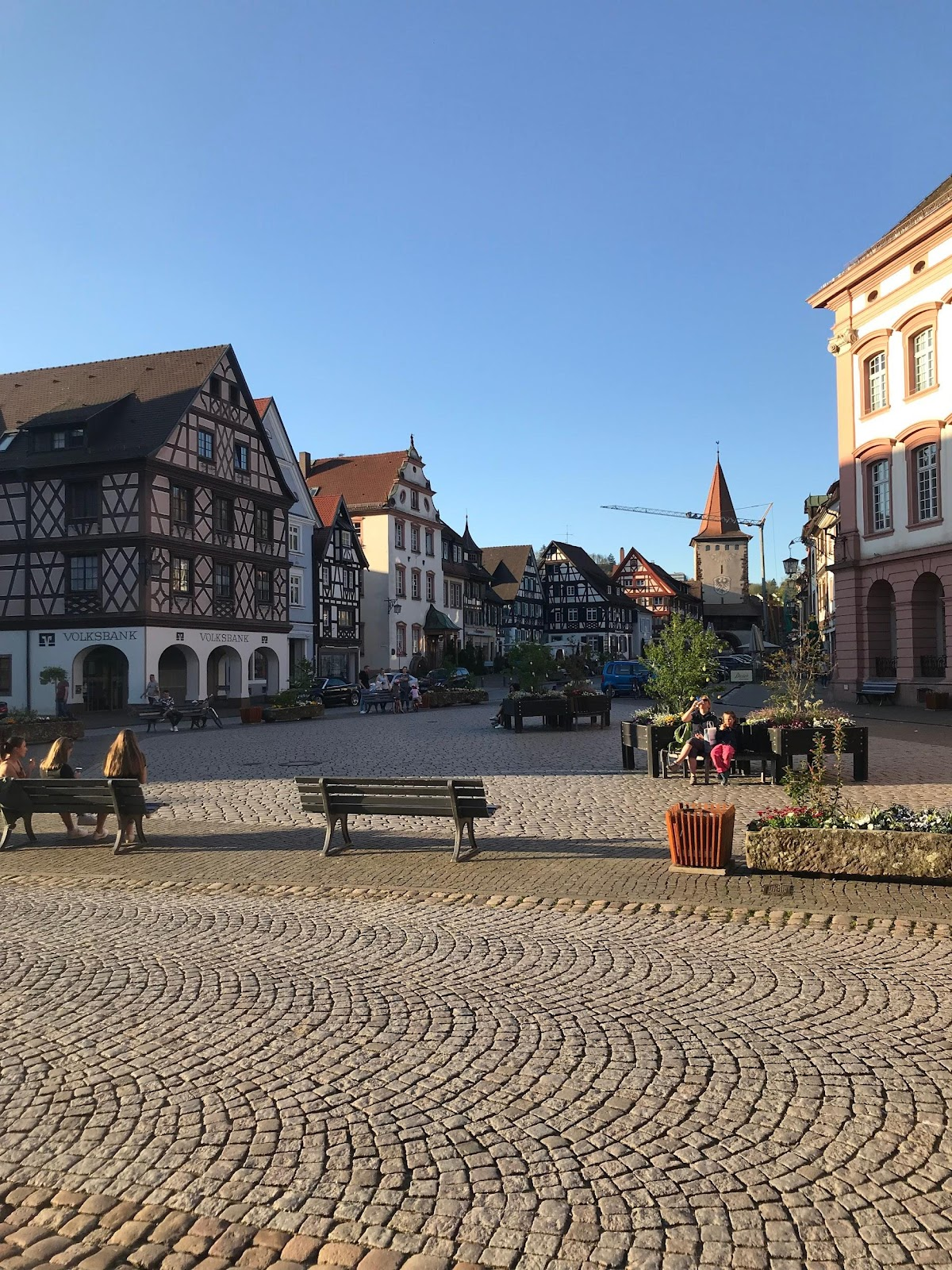 gengenbach medieval city center traditional bavarian wooden bright buildings small square people on benches on a clear sunny day in germany