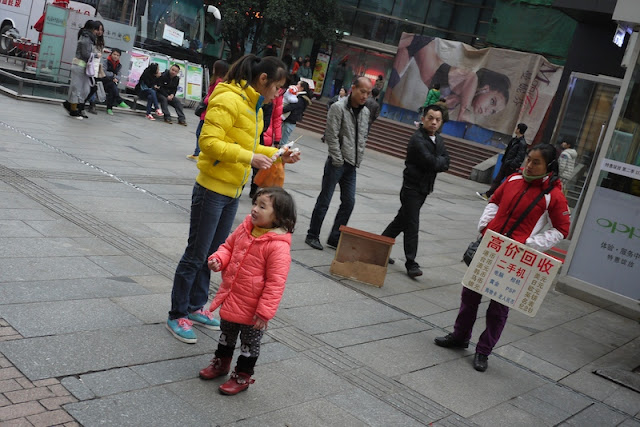 young girl with mother standing behind her in Changsha, China