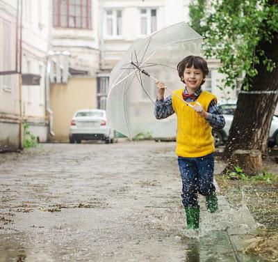 Anak kecil bermain hujan