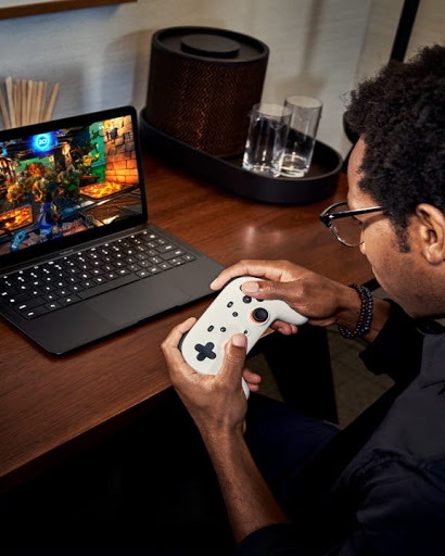 An over the shoulder shot of a young man using his Stadia controller to game on his laptop.