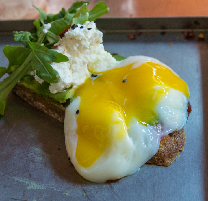 close-up photo of the poached egg served with avocado toast