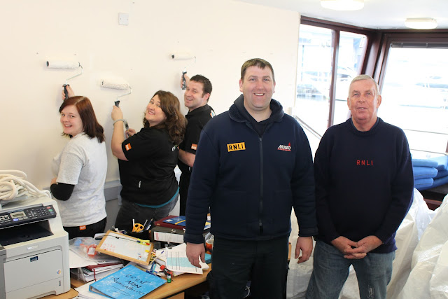 The B&Q 'just do it' team making over Poole Lifeboat Station and just doing it! Poole Mechanic Paul Taylor and Rod Brown, Lifeboat Operations Manager, don't seem to be doing anything! I see no paint brushes or hard work by them! 22 February 2013 Photo: RNLI/Claire-Marie Mason