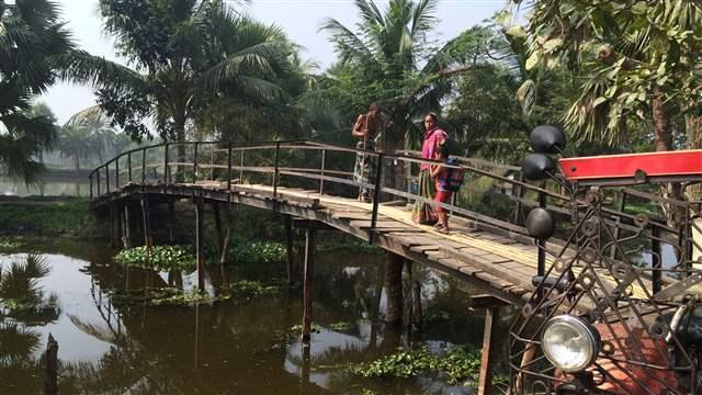 Two people stand on a wooden foot bridge in Khulna, Bangladesh in January 2016. Khulna is a sprawling coastal zone city that has absorbed displaced people from Bangladesh's coastal zone. Photo: Timmons Roberts / Brookings