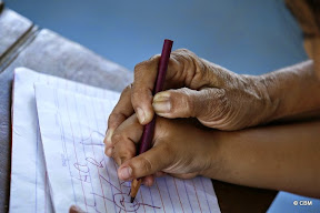 Hand of a young child writing, being guided by an older person's hand.