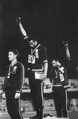 photograph of Tommie Smith (center) and John Carlos (right) raising gloved fists during the medal ceremony for the 200-meters at the 1968 Olympic Games in Mexico City