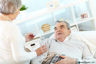 Portrait of mature woman giving tablets and glass of water to her sick husband at home