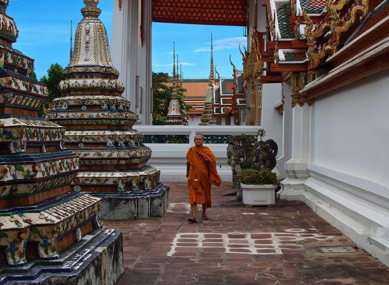 Tibetan monk walks between the pillars of the temple.