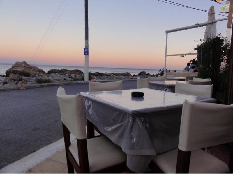 Et tomt bord på et fortau med havet og en skumrende himmel i bakgrunnen.