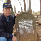 Results of the lesson for reading old gravestones: Owen Gleaves holds the gravestone of Guy Trigg Gleaves, a distant relative.  Notice how easy it is to read the stone after flour has been dusted over it.