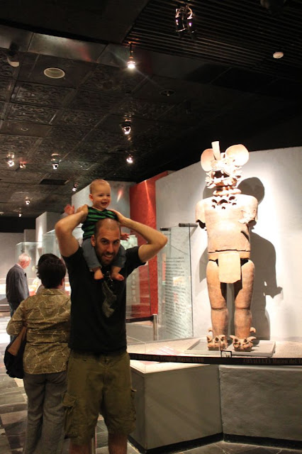 at the templo mayor museum with baby on shoulders