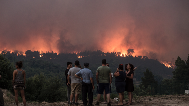 People observe as fire gets closer to the village of Monchique, in southern Portugal's Algarve region, Sunday, 5 August 2018. Photo: Javier Fergo / AP Photo