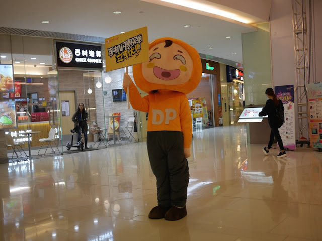 male Dianping mascot holding a sign at a Changsha mall