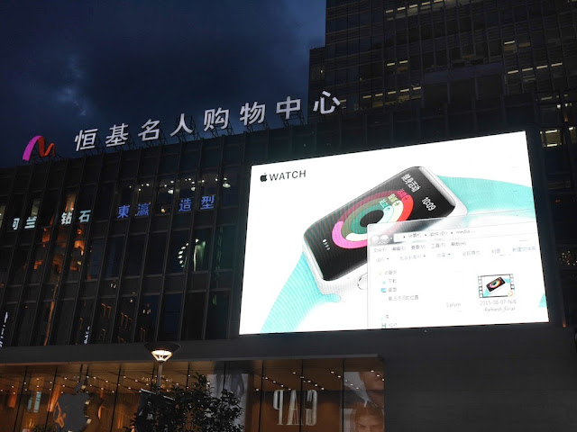 Apple Watch advertisement on large video screen with an open Windows folder visible above an Apple Store in Shanghai
